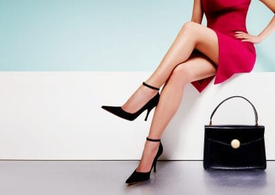 Beautiful legs woman wearing red dress with a black purse hand bag with high heels shoes sitting on the white bench. with copyspace.